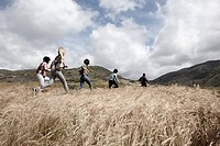Group of young friends running in field