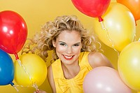 Young blonde woman with balloons against yellow background (thumbnail)