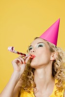Young woman wearing party hat with party blower (thumbnail)