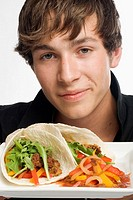 Young man picking up a taco off of plate
