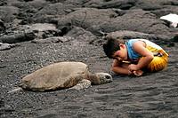 Hawaiian boy observes green sea turtle, Chelonia mydas, Black Sand Beach, Big Island, Hawaii, USA