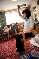 Elderly residents of a sheltered housing scheme doing light exercises while seated, UK