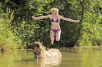 girl jumping into water from her Icelandic horse