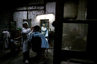 Elderly barber giving his client a haircut in a traditional barbershop, Shanghai, China