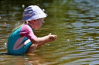 Four year old girl playing in the waters of a lake