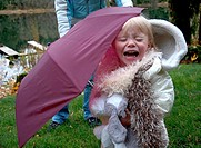 This two year old Caucasian toddler girl is crying outside under a burgundy colored umbrella She's wearing a white coat and white furry scarf and hold...