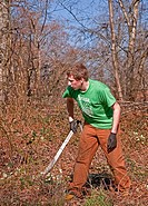 his young Caucasian man in his early twenties is working hard to clear brush off the land with a machete knife His arms are scratched and bleeding fro...