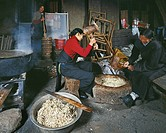 Tibetan people smashing the stellera chamaejasme roots for making paper, Dege Sutra Printing House, Garze, Sichuan, China
