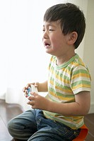 Crying little boy holding toy bus