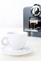 espresso on coffee maker and coffee cup