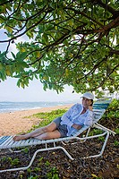 Woman relaxing on sun lounger at the beach, Kauai, Hawaii, USA