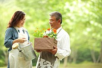 Mature husband and wife carrying flowers in their back yard
