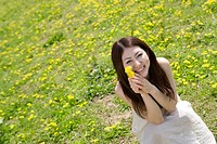 Portrait of young woman in field of dandelions, Kyoto prefecture, Japan