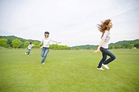 Four young people running in field, pretending to be airplane, Shiga prefecture, Japan