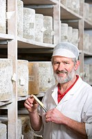Portrait of smiling cheese maker holding cheese iron with sample of farmhouse cheddar