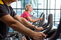 Smiling senior woman riding exercise bike in health club