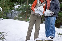 Couple holding large snowballs in woods