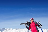Woman holding skis and ski poles on snowy mountain