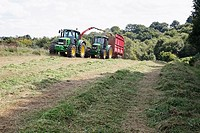 Two tractors collecting cut grass for silage at Talke, Stoke-on-Trent, Staffordshire