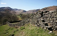 A stile in a dry stone wall looking towards Great Langdale Fells near to Elterwater in the Lake District National Park, Cumbria, England