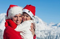 Mother and dauhter wearing Santa hats, hugging