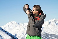 Young man in ski wear taking photos