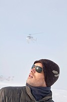 Portrait of young man in winter clothes looking up, helicopter in background