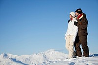 Young couple embracing in snow