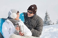 Young couple in ski wear resting
