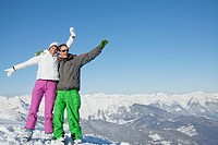 Young couple in ski wear smiling at camera
