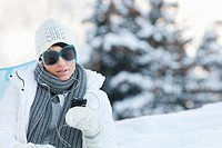 Young woman listening to MP3 player in snow