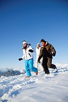 Couple and daughter in ski wear running in snow