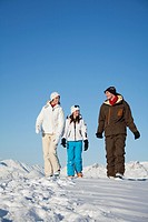 Couple and daughter in ski wear walking in snow