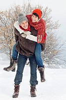 Young man giving his girlfriend piggyback in snow