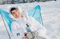 Young woman resting in snow, smiling at camera