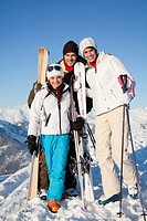 Couple and daughter holding skis, smiling at camera