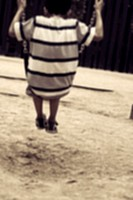 niño de espaldas columpiándose en el columpio del parque infantil. Imagen de nostalgia