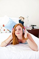 Beautiful teenager listening to the music on the bed