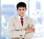 Self_assured businessman with folded arms standing in the office