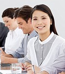 Smiling businesswoman in a meeting with her team looking at the camera