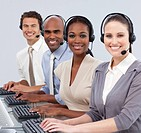 Multi_ethnic business people with headset on smiling at the camera in a call center