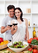Smiling couple toasting and cooking in the kitchen