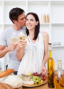 Smiling lovers toasting with white wine in the kitchen