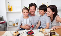 Young family eating fruits and pancakes for breakfast in the kitchen