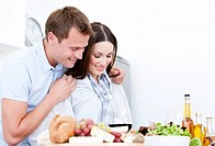 Portrait of Cute couple preparing a meal in a kitchen