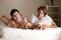 Man and woman reading a magazine on bed, low angle view