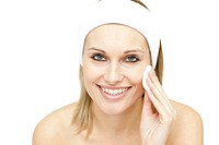 Smiling woman putting foundation cream against a white background