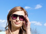 Portrait of an attractive blond woman with sunglasses outdoors