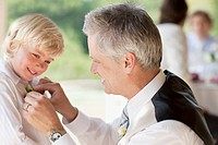 Father adjusting son's tie at party