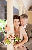 Mature bride and groom hugging